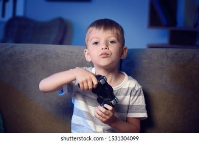 Cute little boy playing video games at home in evening