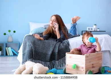 Cute little boy playing while young nanny talking on mobile phone, indoors