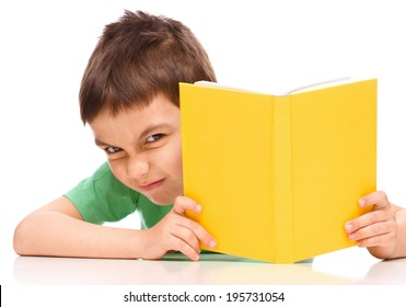 Cute little boy plays with book while sitting at table, isolated over white