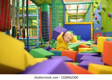 Cute little boy plays with soft cubes in the dry pool in play center. Kid playing on indoor playground in foam rubber pit in trampoline. Child having fun in entertainment center.