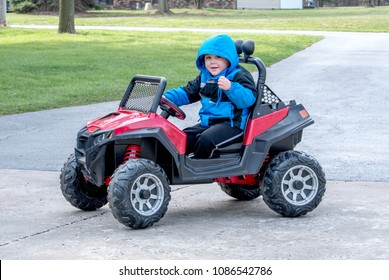 a cute little boy poses as he drives a battery powered jeep down the driveway