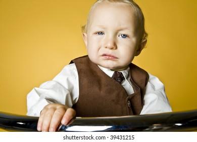 Cute little boy posing on yellow background.