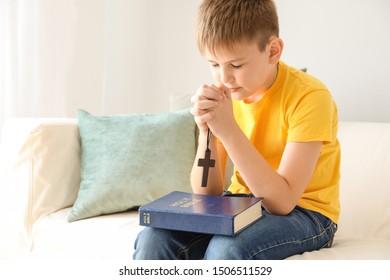 Cute little boy praying at home
