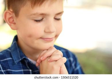 Cute little boy praying outdoors