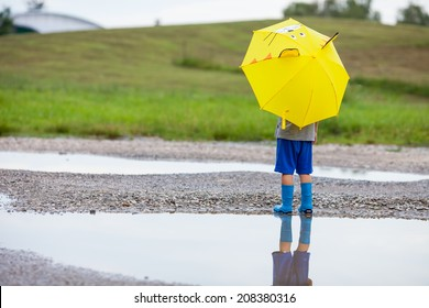 Cute little boy in the puddle with blue boots and yellow cat umbrella after the summer rain