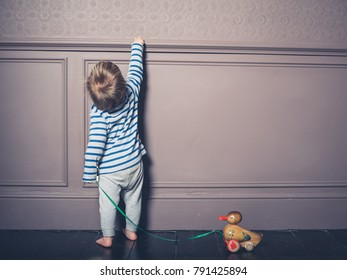 A cute little boy is pulling a wooden duck toy