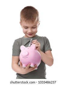 Cute little boy putting money into piggy bank on white background