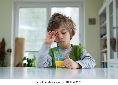 Cute little boy in pyjama still sleepy sitting at the table drinking orange juice for breakfast. Healthy lifestyle, nutrition and healthy eating