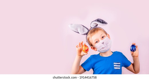 Cute little boy in rabbit bunny ears on head and protective mask with colored eggs on pink background. Cheerful smiling happy child. Covid Easter holiday banner