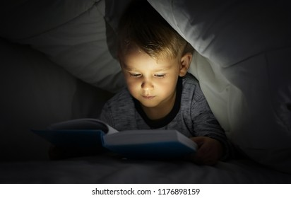 Cute little boy reading book in bed under blanket