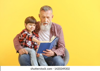 Cute little boy reading book with grandfather on color background