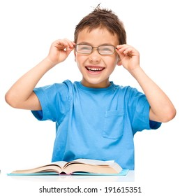 fd8b2788b4731e Cute little boy is reading a book while wearing glasses