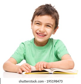 Cute little boy is reading a book, isolated over white