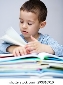 Cute little boy is reading book while sitting at table
