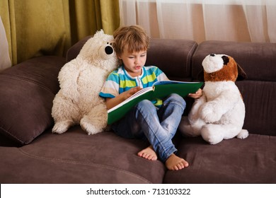Cute little boy is reading book  with plush toys sitting on a sofa at home