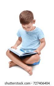 Cute little boy reading book on white background