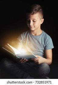 Cute little boy reading book on black background