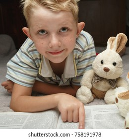 cute little boy reading book with his favorite toys on a soft plush blanket, looking at camera