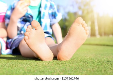Cute little boy relaxing in park on sunny day