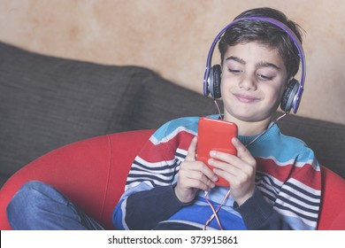 Cute little boy relaxing while listening to music. Toned image with shallow depth of field