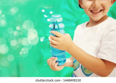 Cute little boy with reusable water bottle. Concept of awareness of the plastic pollution world, the future for our children. Zero waste. Green background