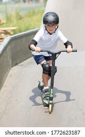 Ein süßer kleiner Junge fährt einen Roller in einem Skatepark. Ein junger Anfänger verbringt Freizeit im Extremsport. Lifestyle.
