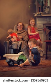 Cute little boy is riding a kitty in a toy truck. The kitty doesn't want to sit in truck. Grandmother and her grandchildren are laughing.  Image with noise effects, selective focus and toning.