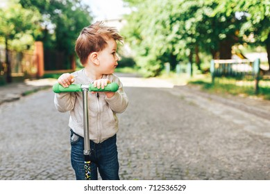 Cute little boy riding scooter outdoor on the street
