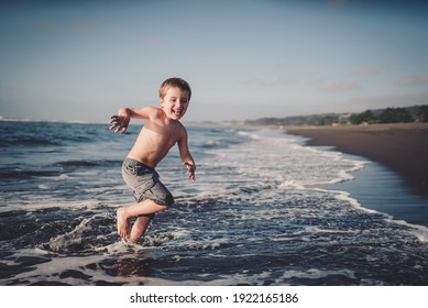 Cute little boy running and playing at the sea shore