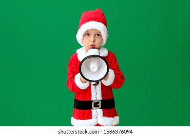 Cute little boy in Santa costume and with megaphone on color background