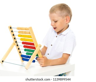 A cute little boy at school at a table studying mathematics. He uses abacus to solve mathematical problems. The concept of teaching a child in the family or at school.Isolated on white background.