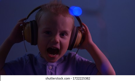 Cute little boy screaming and enjoying listening to music. Portrait, face. Neon colors