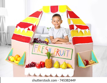 Cute little boy selling fruits at counter indoors