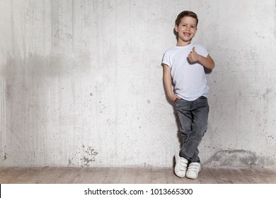 Cute little boy showing gesture thumb up. Portrait of smiling male child in gray trousers and white T-shirt. Positive little guy, gray wall on background, copy space.