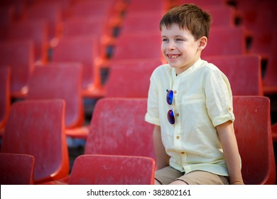 Cute little boy sits on a tribune. Stadium in the open air, summer.