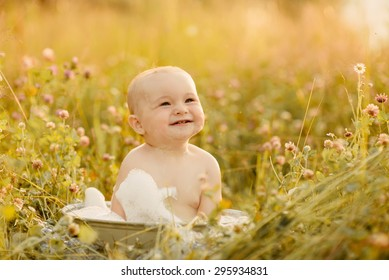 cute little boy sitting in a basin on the nature and bathed in summer