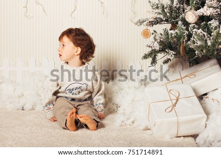 686d0cb7a6cc Cute little boy is sitting with a gift near the Christmas tree. The child is