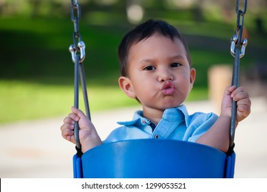 Cute little boy sitting and holding on to a blue swing while blowing kisses with lips puckered up.