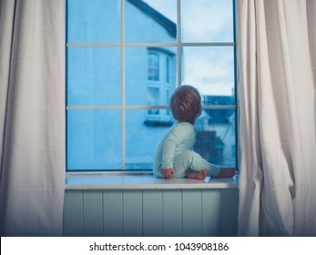 A cute little boy is sitting on the window sill in the morning