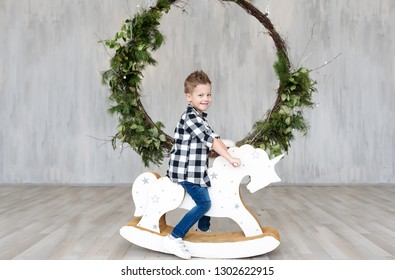 Cute little boy sitting on a wooden toy horse in an interior of studio. Horizontal portrait