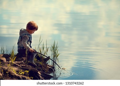 Cute little boy is sitting on the shore with a stick. There is a cloud sky reflecting in the water. Image with selective focus and toning