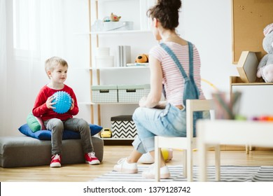 Cute little boy sitting on pouf and holding blue ball during ADHD therapy