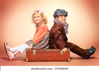 Cute little boy is sitting on the old suitcase with charming little lady. Retro style.