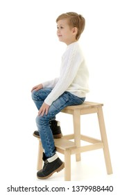 A cute little boy is sitting on a chair. Isolated on white background.