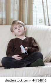 cute little boy sitting on the sofa and watching tv with a remote control