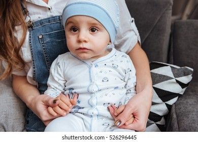 Cute little boy sitting on his mother hands at home