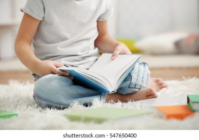 Cute little boy sitting on the carpet with book on blurred background