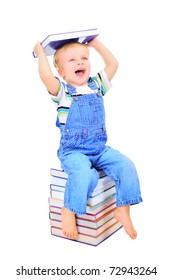 Cute little boy is sitting on a heap of textbooks