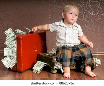 Cute little boy sitting ?n a suitcase with the money