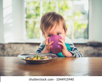A cute little boy is sitting at the table drinking from a cup